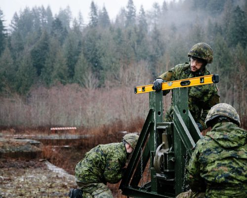 Canadian Army Reserve combat engineers level the roller beam assembly in preparation of building a Medium Girder Bridge