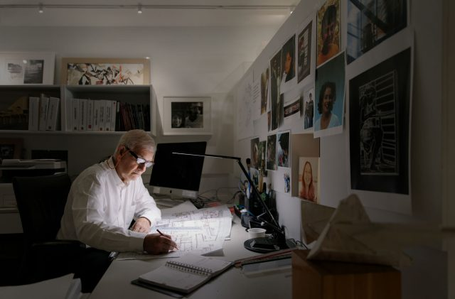 Wide angle photo of Richard Henriquez, founding principal of Henriquez Partners Architects at work at his desk in Vancouver, BC.