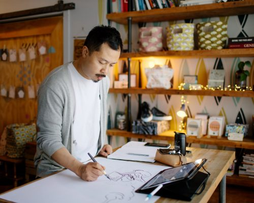 Artist Carson Ting drawing in his studio