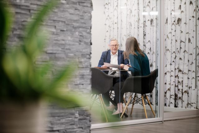 A male and female in conversation inside of an office