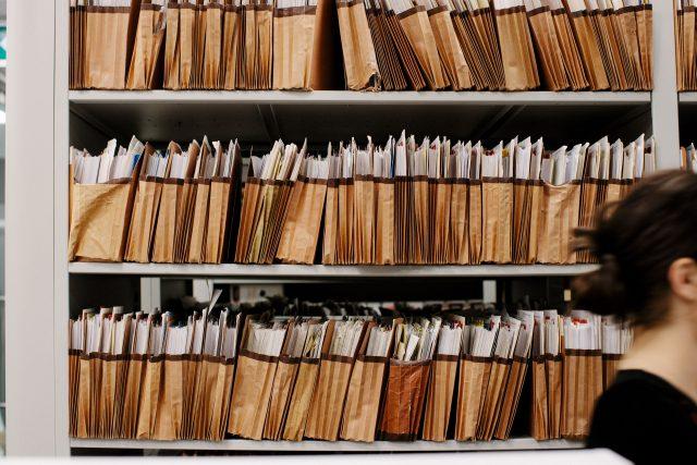Woman walking past a shelf full of files