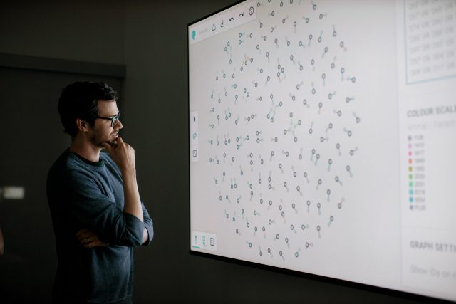 Man stands in front of large projector screen studying medical information