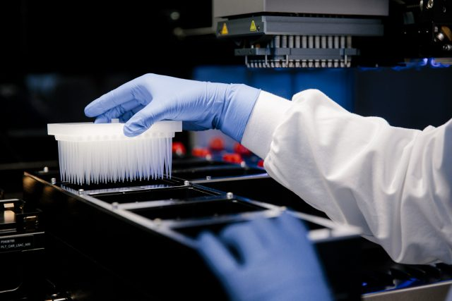 Close up of hands interacting with medical lab equipment used to research antibodies