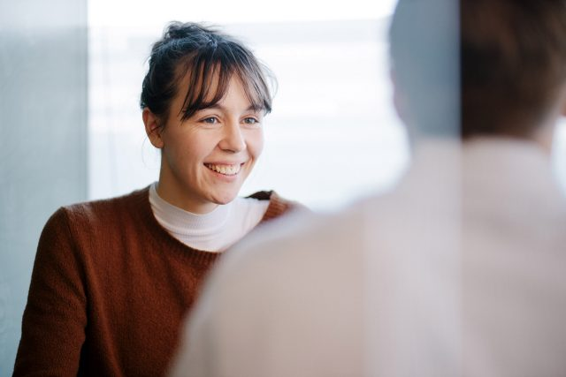 A young caucasian woman in conversation with a male colleague in an office