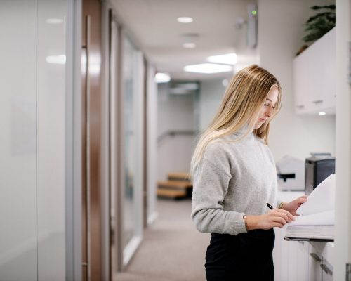 Young caucasian female writing in open binder in hallway of law firm