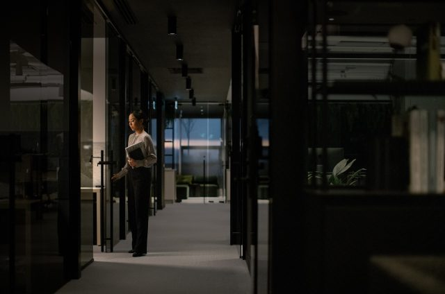 Young asian woman opens glass door in modern office