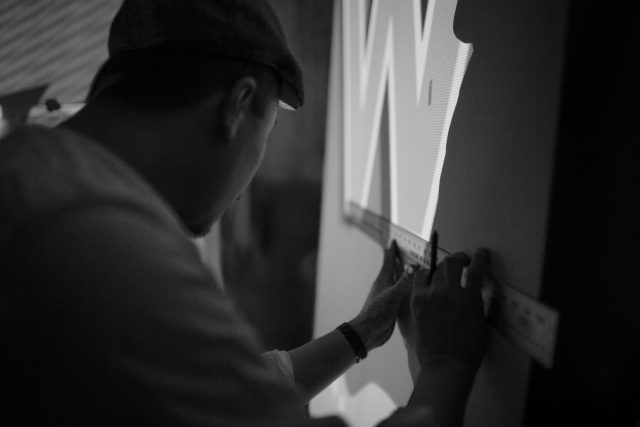 Asian illustrator works on a mural in his studio