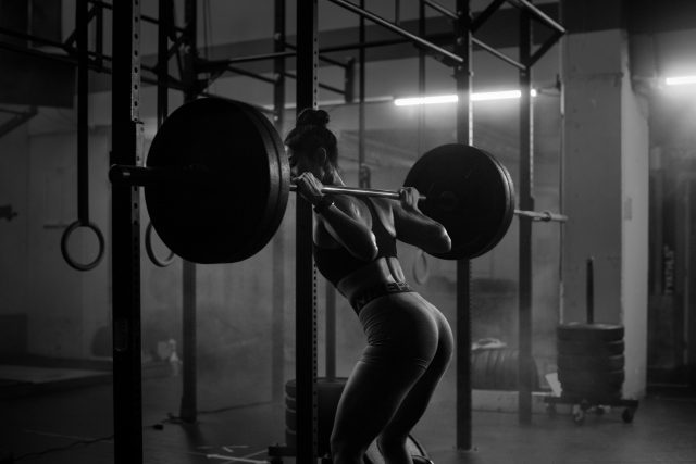 Asian woman working out with barbell in Vancouver indoor gym wearing nike pro clothing