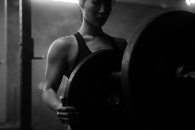 Asian woman moving weight plates in Vancouver indoor gym wearing nike pro clothing