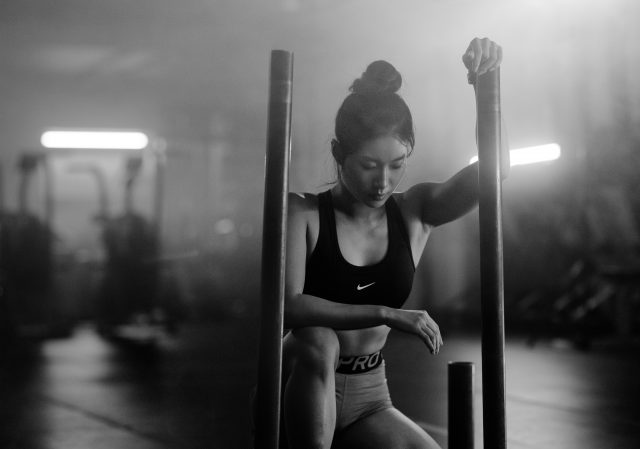 Asian woman working out with weight sled in Vancouver indoor gym wearing nike pro clothing