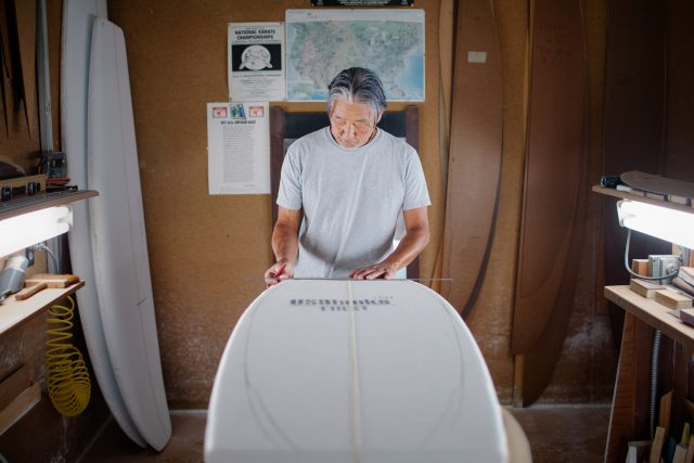 Asian man shapes surfboard in his workshop