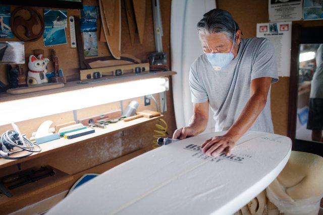 Asian man crafting a surfboard in his workshop