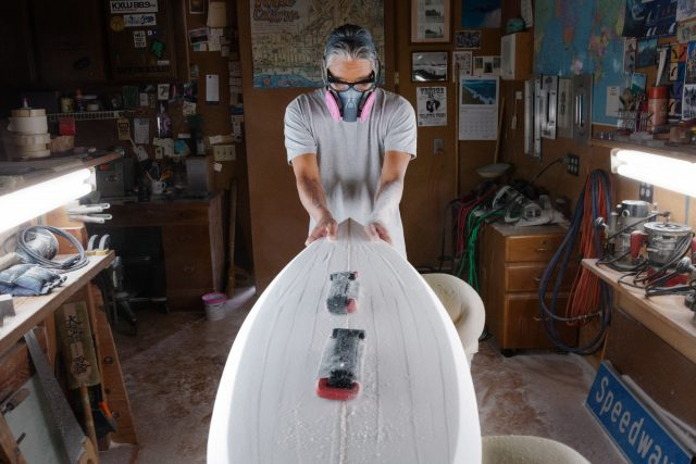 Asian man crafts a surfboard in his workshop