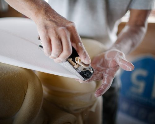 Close up photo of artist shaping a surfboard inside workshop