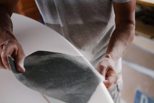 Close up detail of artist sanding edges of a surfboard under construction